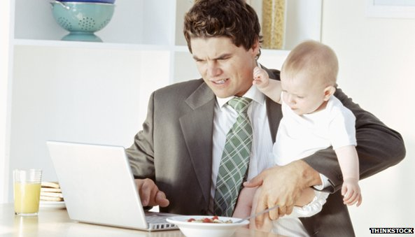 Man Working with Baby at Computer