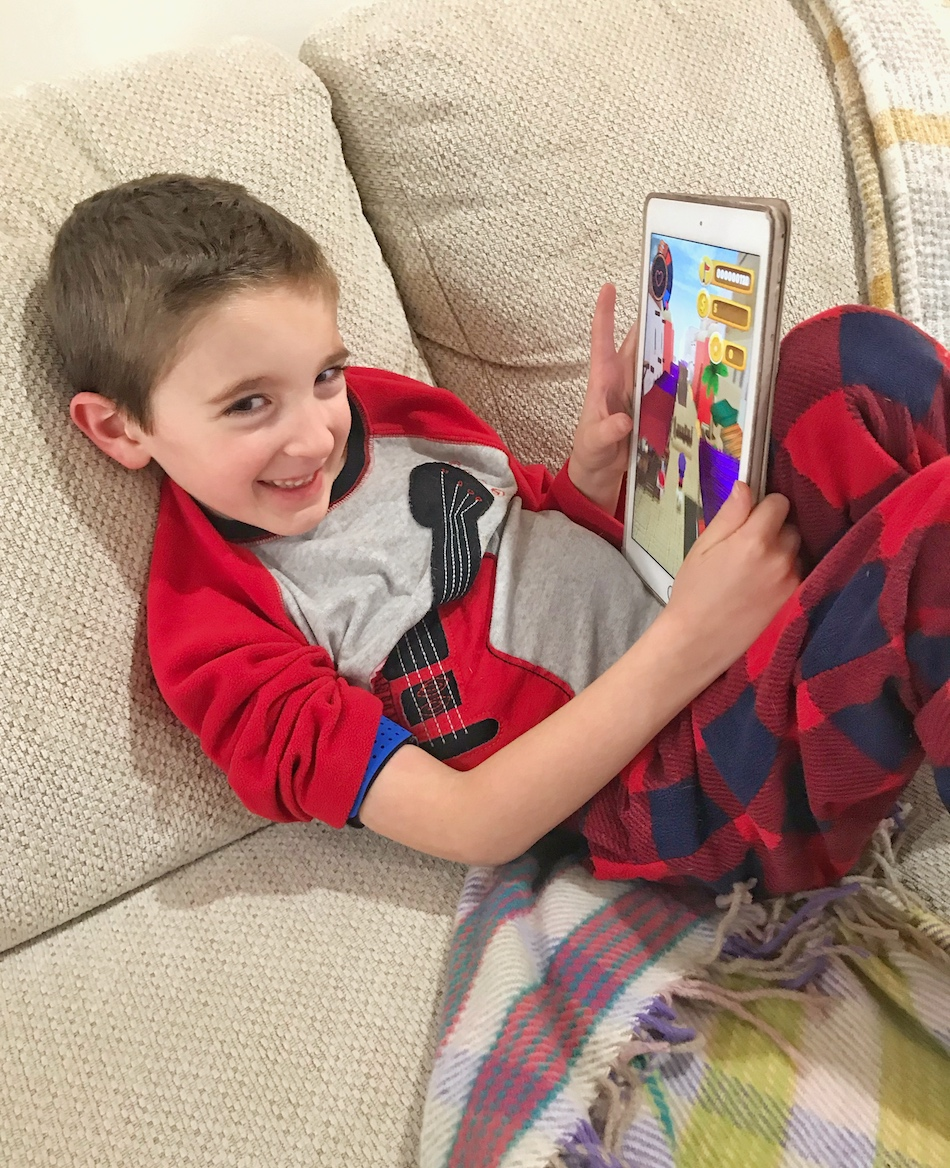 Boy playing Mightier app - boy showing iPad smiling