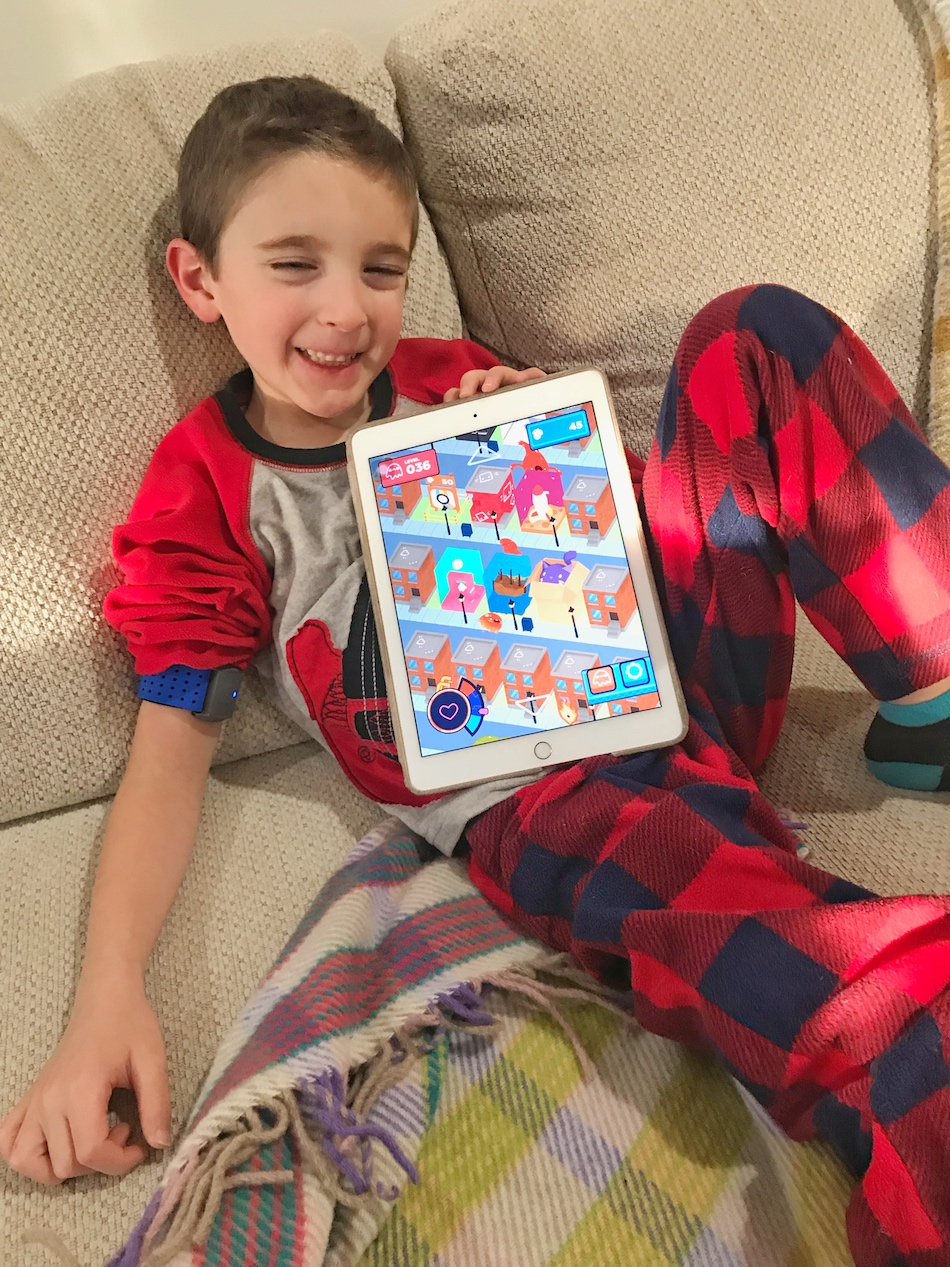 Boy playing Mightier app - boy smiling with app home open